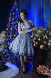 Teen girl in Christmas at the beautiful Christmas tree g. Lowing in the dark Stock Images