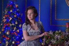 Teen girl in Christmas at the beautiful Christmas tree g. Lowing in the dark Royalty Free Stock Photo