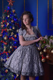 Teen girl in Christmas at the beautiful Christmas tree g. Lowing in the dark Royalty Free Stock Photography