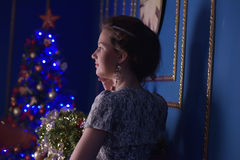 Teen girl in Christmas at the beautiful Christmas tree g Stock Images
