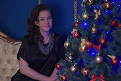 Teen girl in Christmas at the beautiful Christmas tree g. Lowing in the dark Royalty Free Stock Image
