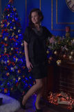 Teen girl in Christmas at the beautiful Christmas tree g. Lowing in the dark Stock Photos