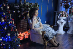 Teen girl in Christmas at the beautiful Christmas tree g. Lowing in the dark at fireplace Royalty Free Stock Image