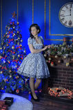 Teen girl in Christmas at the beautiful Christmas tree. Glowing in the dark Royalty Free Stock Photography