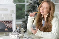Teen girl with Christmas decorations. Portrait of happy teen girl with Christmas decorations sitting at the table at home Royalty Free Stock Images