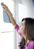 Teen girl cleaning windows inside home Royalty Free Stock Photos