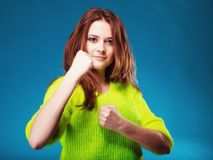 Teen girl clenching fists on blue Royalty Free Stock Images
