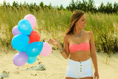 Teen girl with colorful balloons outside Stock Photo
