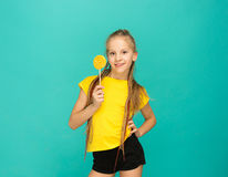 The teen girl with colorful lollipop on a blue background Stock Photos