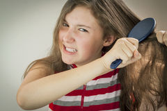 Teen girl combing hair Royalty Free Stock Images