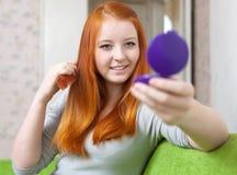 Teen girl combing  hair Royalty Free Stock Photography
