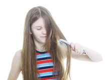 Teen girl combing her long hair Royalty Free Stock Photography