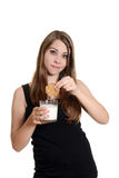 Teen girl with cookie dunked in milk Royalty Free Stock Images