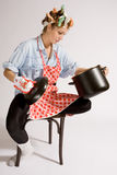 Teen girl cooking. With hair curlers Royalty Free Stock Images