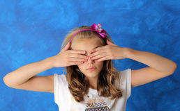 Teen girl covered her eyes with her hands. It stands on a blue background. The girl blonde hair and flower decoration on the head Stock Images