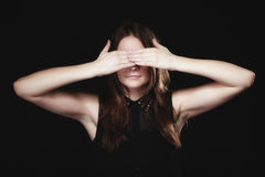 Teen girl covering her eyes on black Stock Photography