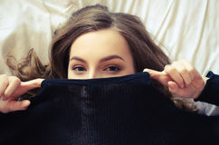 Teen girl covering her face. Portrait of beautiful hipster teenage girl in a knitted black sweater looking at the camera and covering her face with a smile Stock Photos