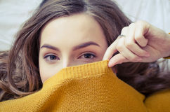 Teen girl covering her face. Portrait of beautiful hipster teenage girl in a knitted orange sweater looking at the camera and covering her face with a smile Royalty Free Stock Photo