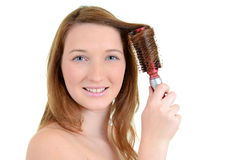 Teen girl curling her hair. Isolated teen girl curling her hair Royalty Free Stock Photo