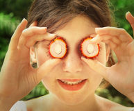Teen girl with cut rambutan fruit half eyes Royalty Free Stock Images
