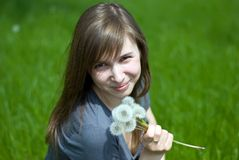 Teen girl with dandelions. Teenage girl on a green meadow with a bouquet of dandelions Stock Images