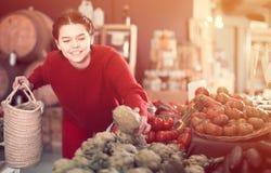 Teen girl decided to buy fresh artichoke Royalty Free Stock Image