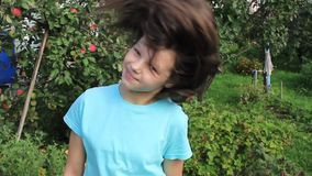 Girl demonstrates her hair on a background of garden. Teen girl demonstrates her hair on a background of orchard stock video