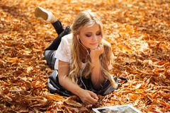 Teen girl with digital tablet lying on leaves Stock Photo