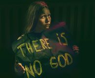 Teen girl with dirty face holding banner with a text - There is no God. Atheistic concept Royalty Free Stock Image