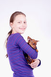 Teen girl with dog in her hands, studio shot Royalty Free Stock Photo