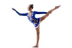 Teen girl doing gymnastic exercise. Beautiful gymnast athlete teenage girl wearing dancer blue dress working out, dancing, posing, doing balance gymnastics royalty free stock photo
