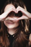 Teen girl doing heart shape love symbol with hands Stock Images
