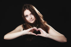 Teen girl doing heart shape love symbol with hands Royalty Free Stock Image