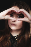 Teen girl doing heart shape love symbol with hands Royalty Free Stock Images