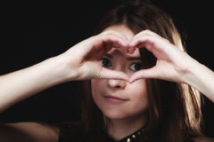 Teen girl doing heart shape love symbol with hands. Love valentine's day concept. Woman teen girl doing forming heart shape love symbol with her hands on black stock photography