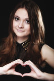 Teen girl doing heart shape love symbol with hands. Love valentine's day concept. Woman teen girl doing forming heart shape love symbol with her hands on black stock images