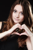 Teen girl doing heart shape love symbol with hands. Love valentine's day concept. Woman teen girl doing forming heart shape love symbol with her hands on black stock image