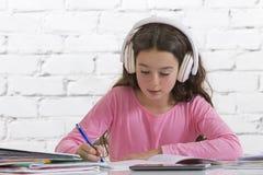 Teen girl doing her homework  with music Stock Photo