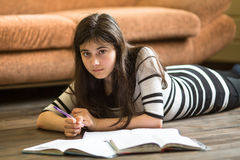 Teen girl doing lessons lying on the floor in the room. Education. Royalty Free Stock Photos