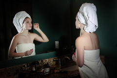 Teen girl doing makeup in bathroom Royalty Free Stock Images