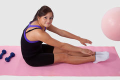 Teen girl doing sit ups. Young brunette aboriginal teen girl wearing workout attire sitting on pink mat reaching for toes stock photo