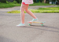 Teen girl down the street with a skateboard Stock Photo