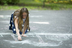 Teen girl drawing with chalk on the pavement. Outside interest. Stock Images