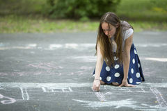 Teen girl draws with chalk on the pavement. Stock Photos