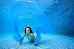 Teen girl in dress posing underwater at the bottom of the pool, playing with a blue cloth, looking at the camera and smiling. Portrait. Shooting under water Royalty Free Stock Photo