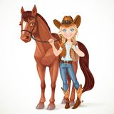Teen girl dressed as a cowboy holds the reins saddled horse Royalty Free Stock Photography