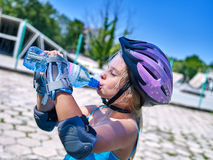 Teen girl drink water and  rides his skateboard. Royalty Free Stock Images