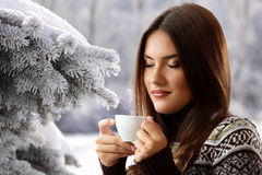 Teen girl drinking coffee over winter nature background Stock Photo