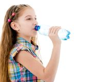 Girl drinking mineral water from bottle. Teen girl drinking mineral water from plastic bottle isolated on white background Royalty Free Stock Photos