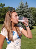 Teen girl drinking water Stock Images